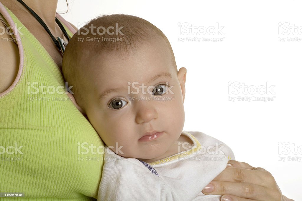 Baby resting in mother's arms stock photo