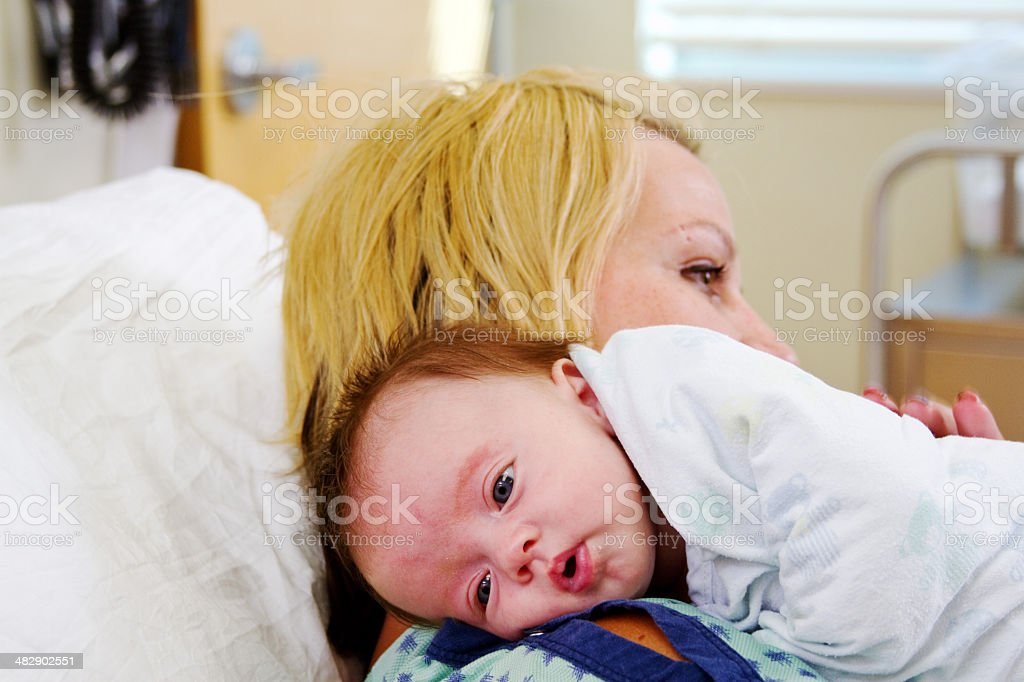 Baby resting on Mom's shoulder stock photo