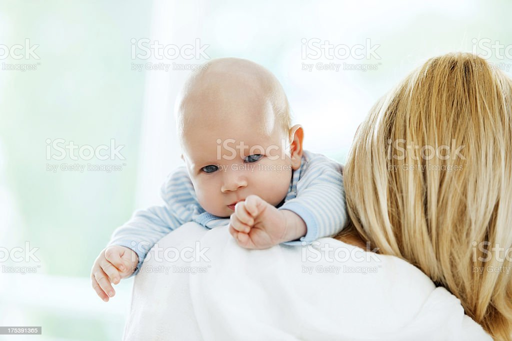Baby resting on mother's shoulder. stock photo