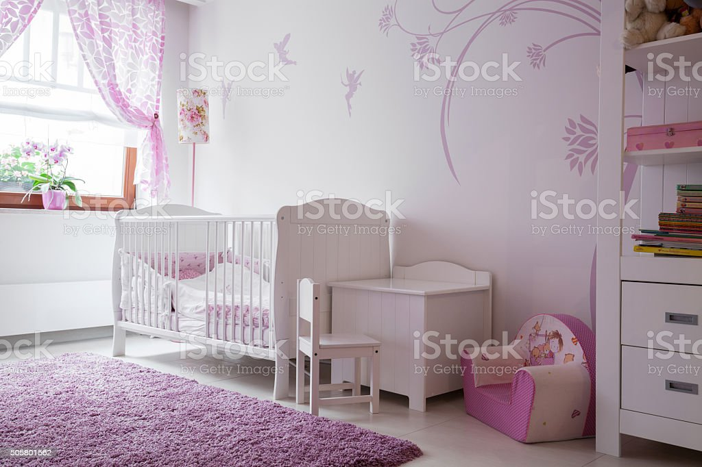 Interior of baby room with white furniture and pink details