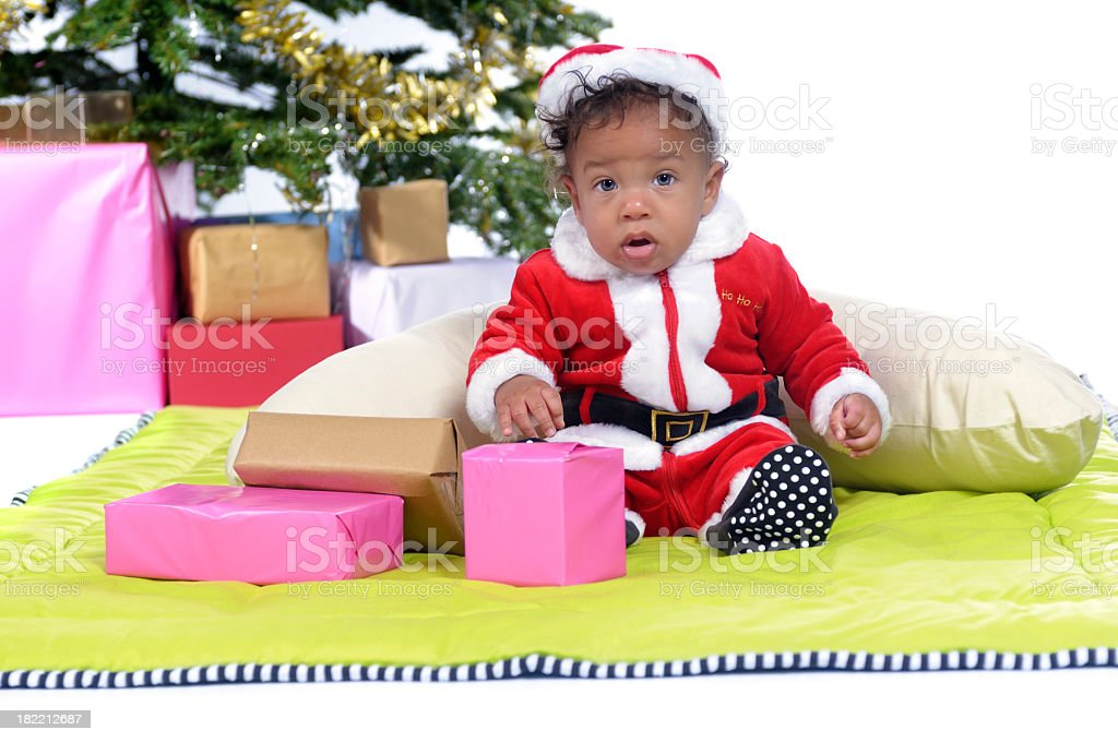Baby Santa Sitting on a Playmat with his Presents stock photo