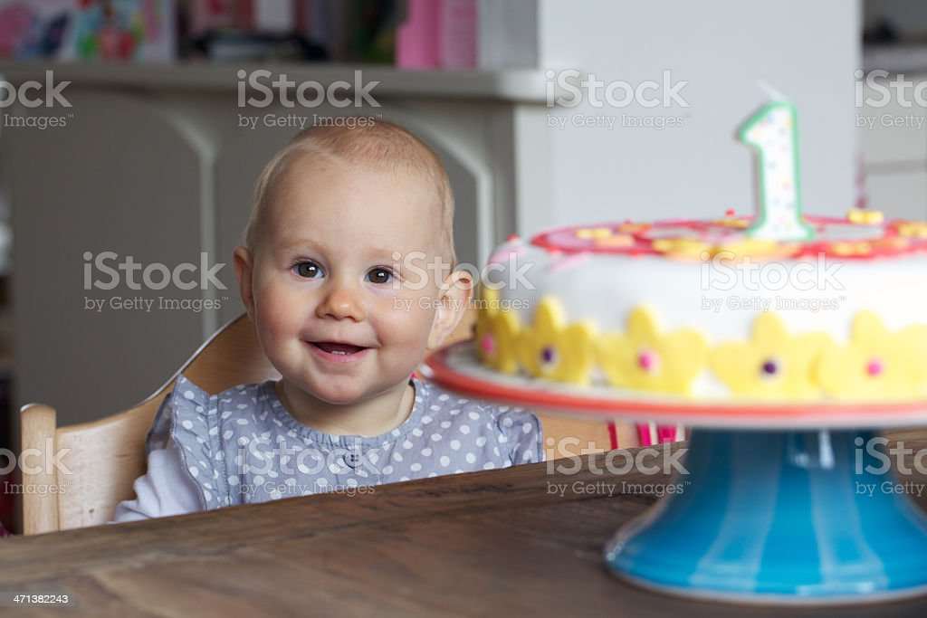 Baby sat at table with birthday cake and number one candle stock photo