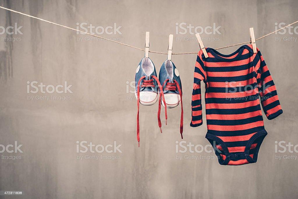 Baby shoes and onesie stock photo
