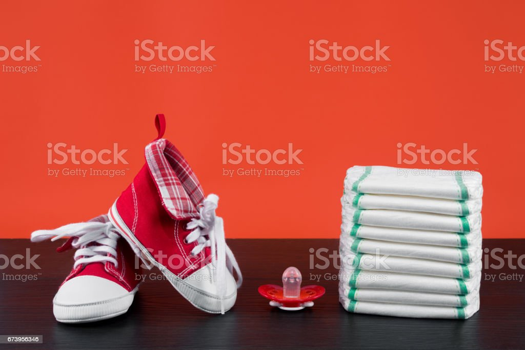 baby shoes, diapers stacked with a pacifier stock photo