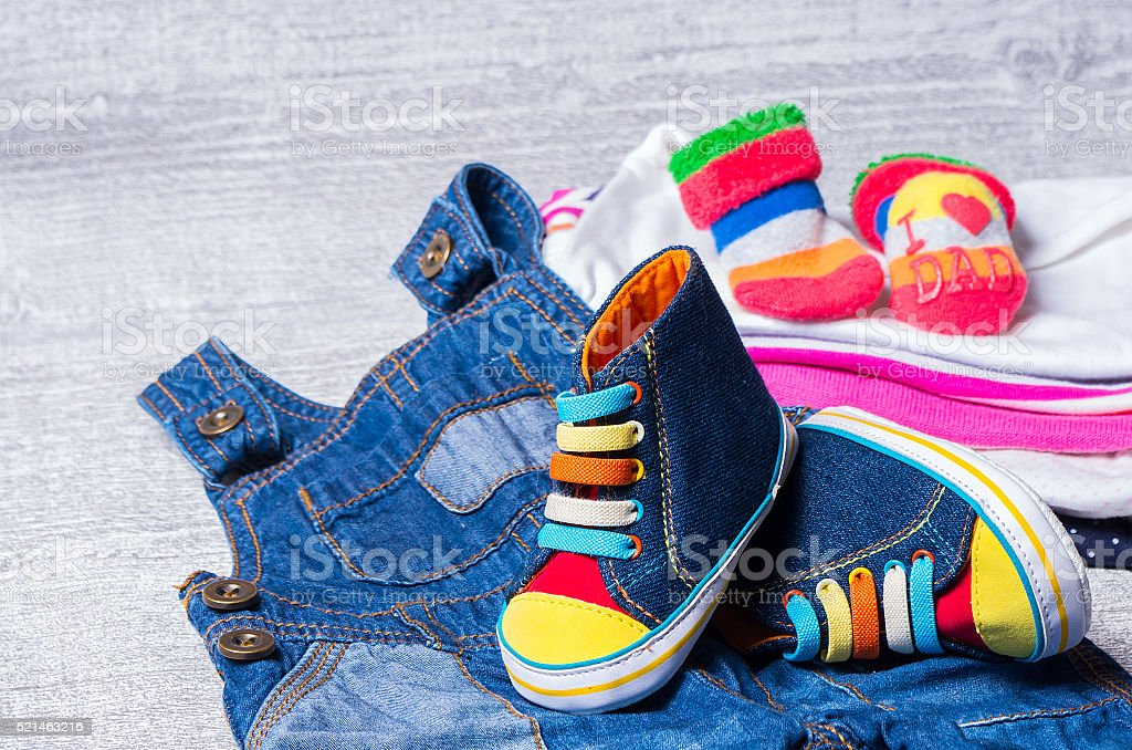 baby shoes for babies and a set of clothes stock photo