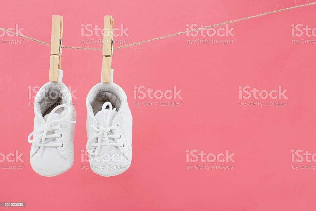 Baby shoes hanging on washing line against pink stock photo