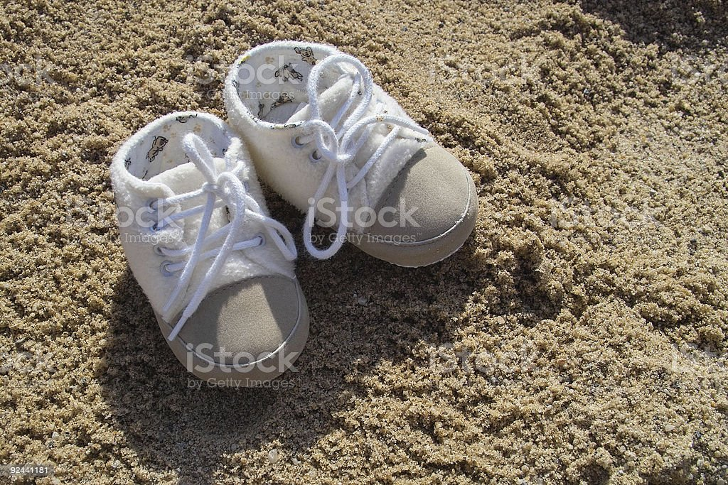 Baby shoes in the sand royalty-free stock photo