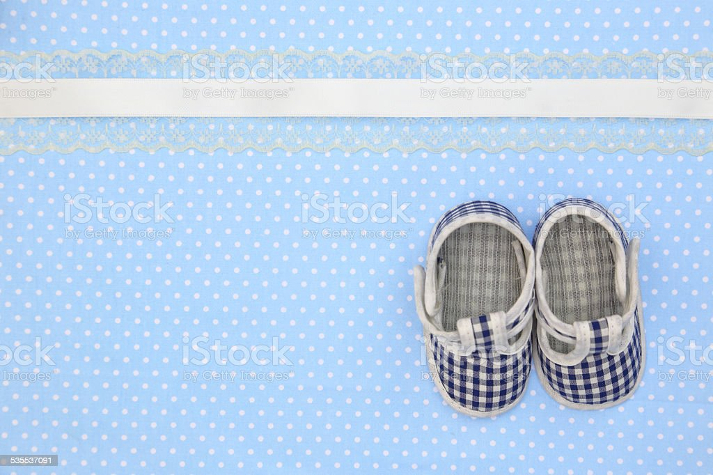 Baby shoes on blue polka dots background stock photo