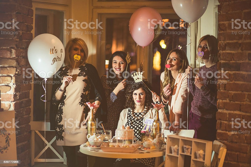 Friends celebrating pregnants woman baby shower opening gift and...