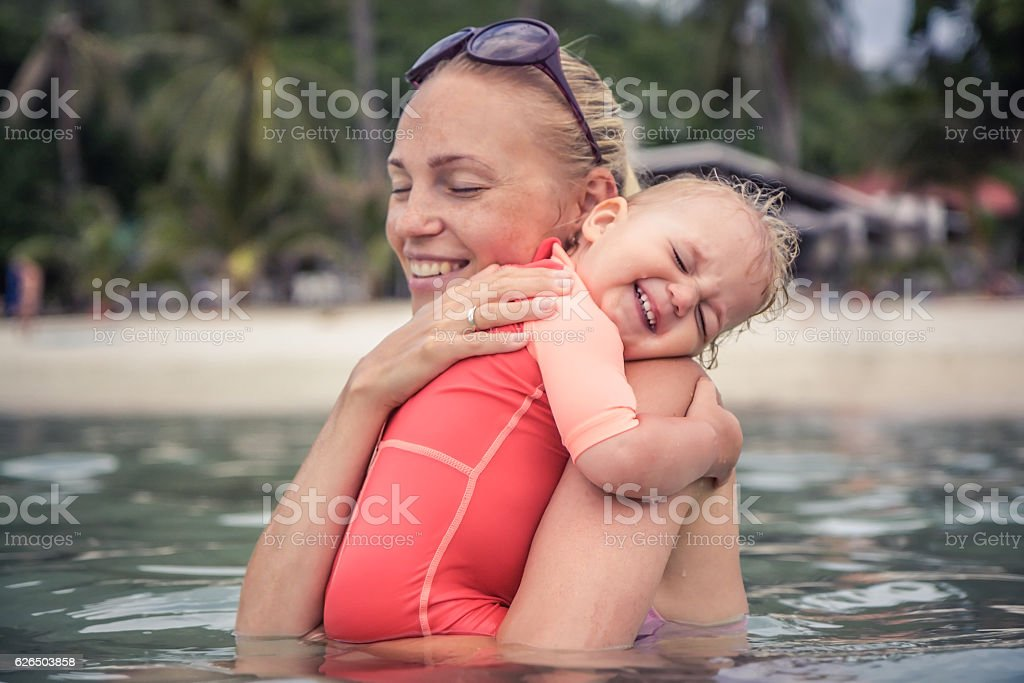 Baby sincerely hugging his mother during beach holidays stock photo