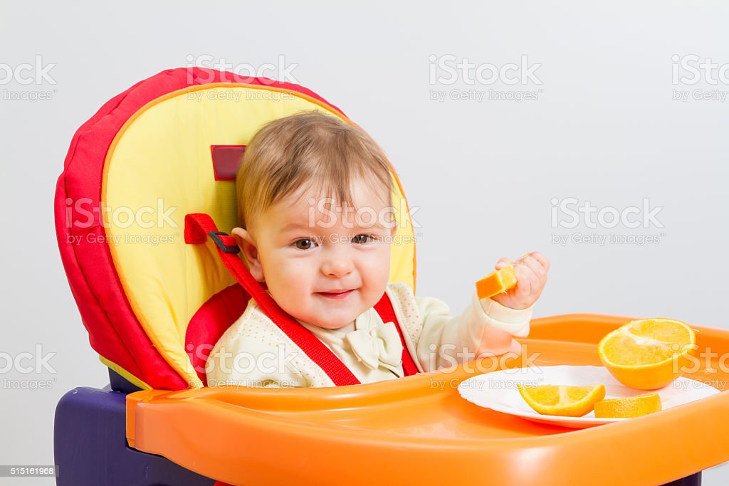 Baby sits in  highchair with orange. stock photo