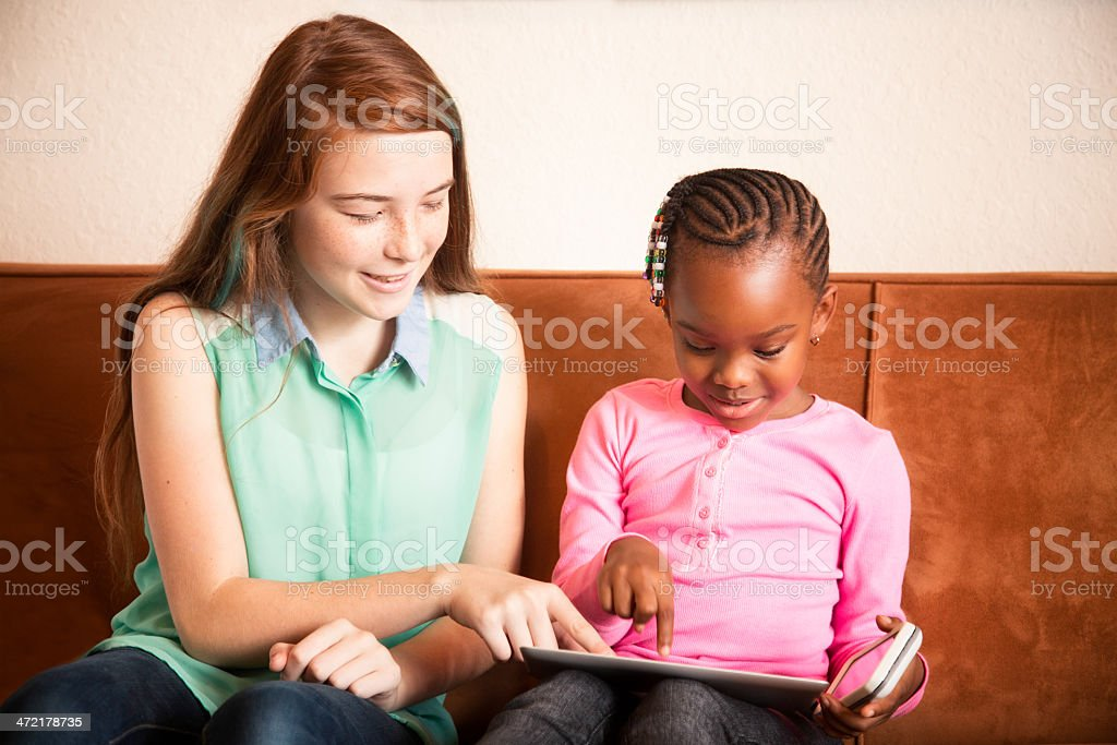 Baby sitter playing with preschooler using tablet mobile phone stock photo