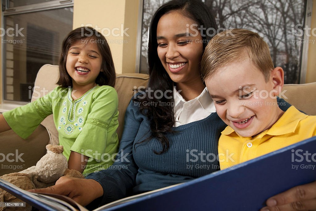 Baby Sitter Reading to Two Children Laughing stock photo