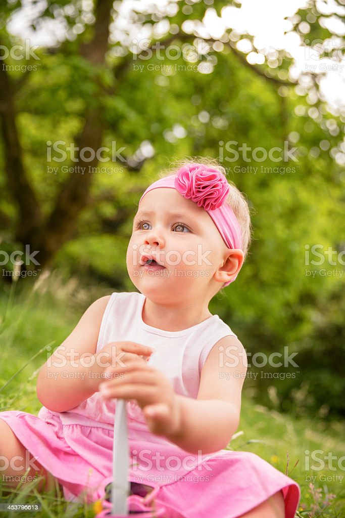 Baby sitting in grass holding heart shaped sunglasses royalty-free stock photo