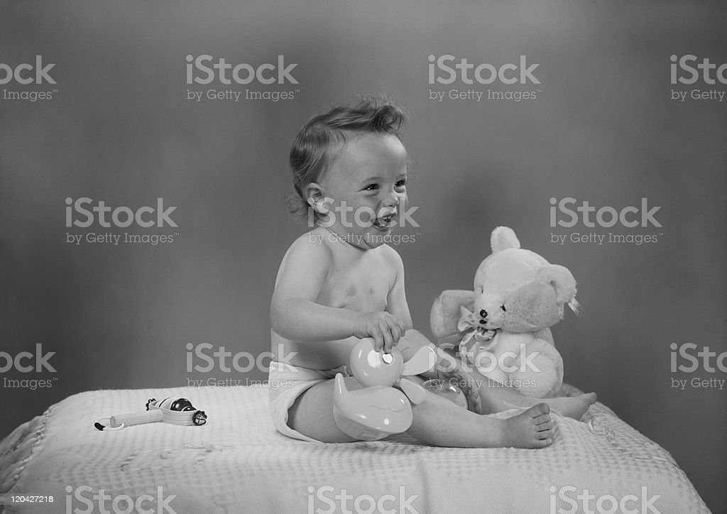 Baby sitting on bed, playing with toys royalty-free stock photo