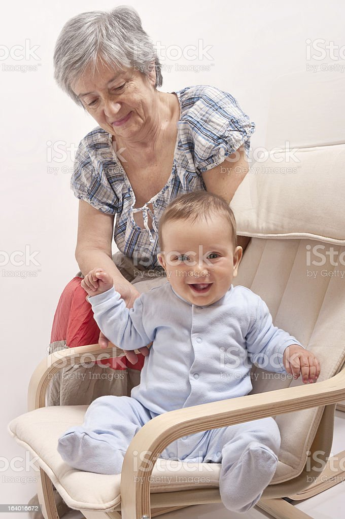 Baby sitting on chair and laughing with grandmother royalty-free stock photo