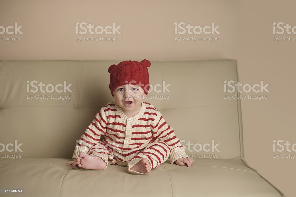 Baby Sitting on Couch Wearing Knit Bear Hat royalty-free stock photo