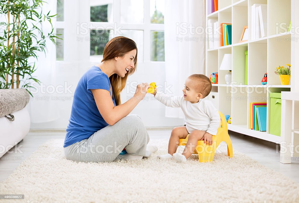 Baby sitting on potty and playing with smiling beautiful mother stock photo
