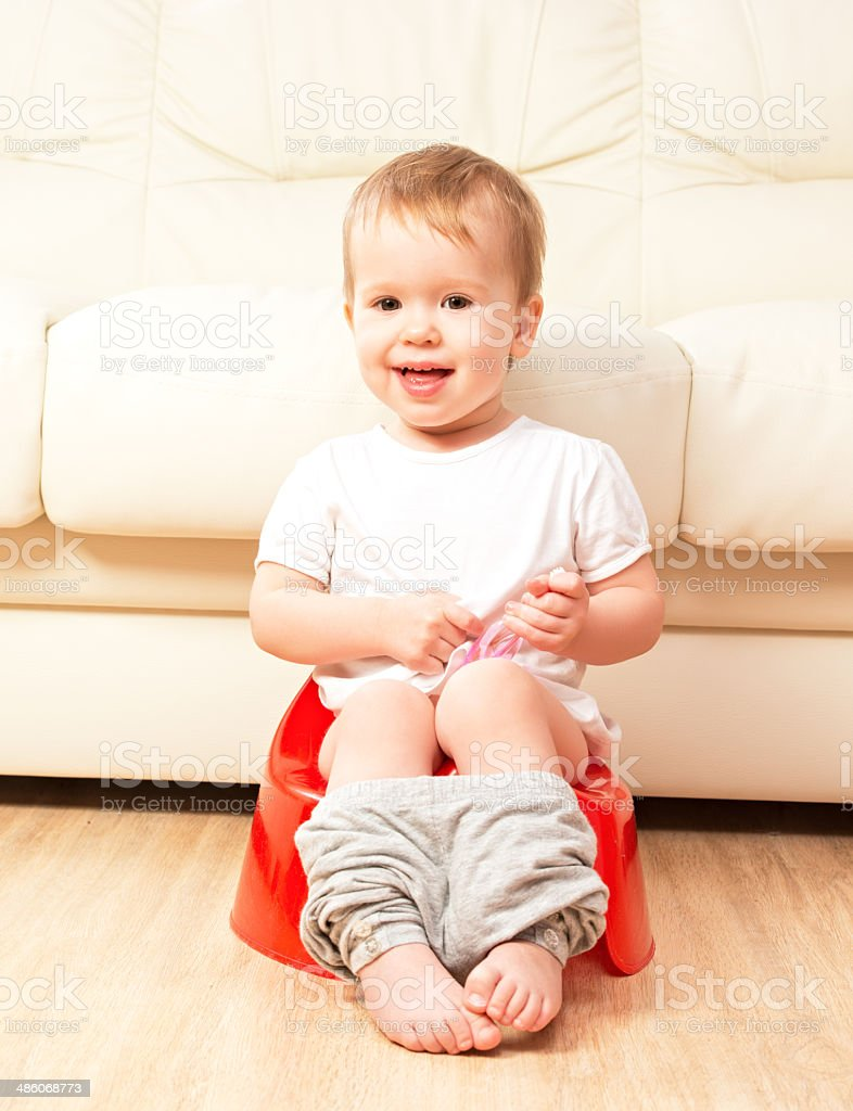 baby sitting on potty in toilet stock photo
