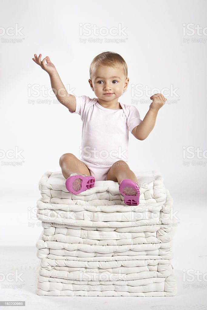 Baby sitting on stack of pillows stock photo