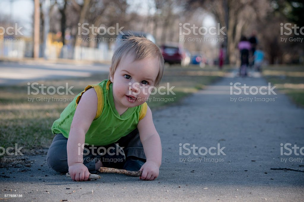 baby sitting outdoors stock photo