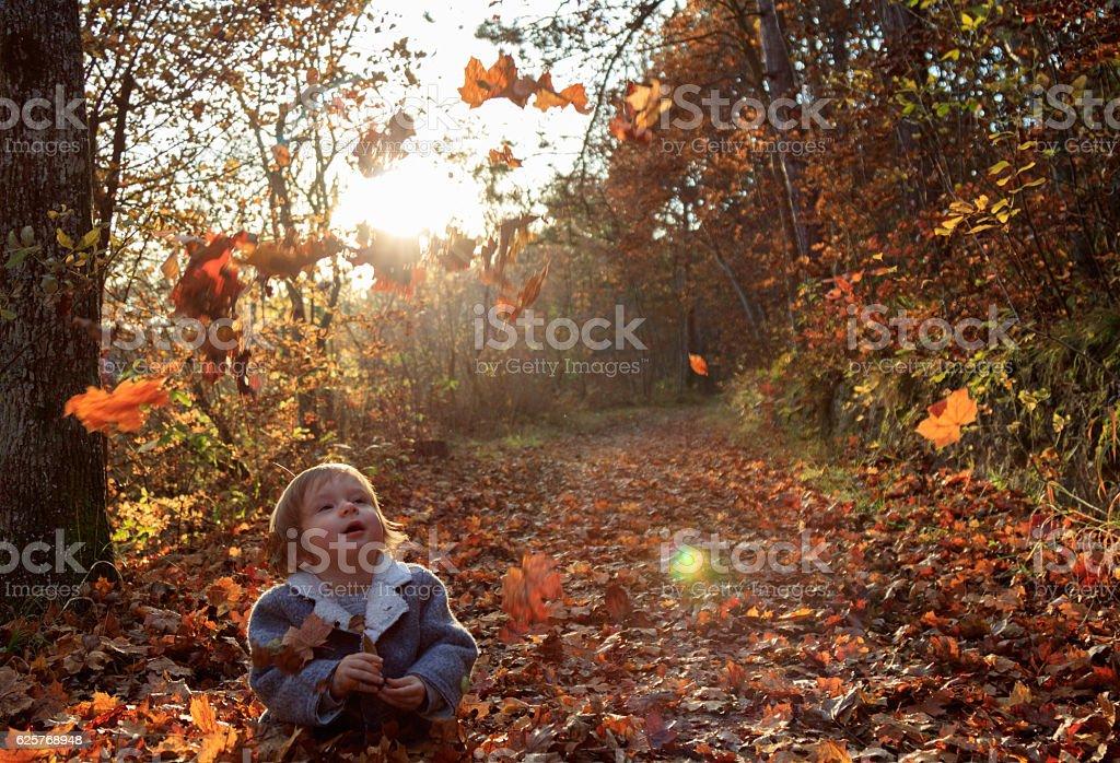 Baby sitzt auf Blättern stock photo