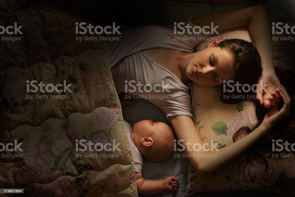 Baby sleeping a deep sleep with her mother stock photo