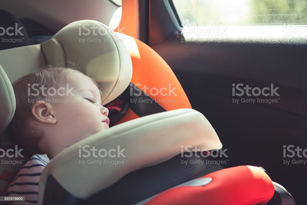Baby sleeping in car safety seat while travelling stock photo