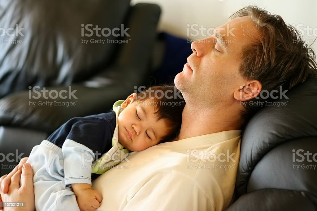 Baby sleeping on dad's chest stock photo