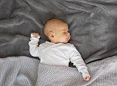 Baby sleeping on grey blanket