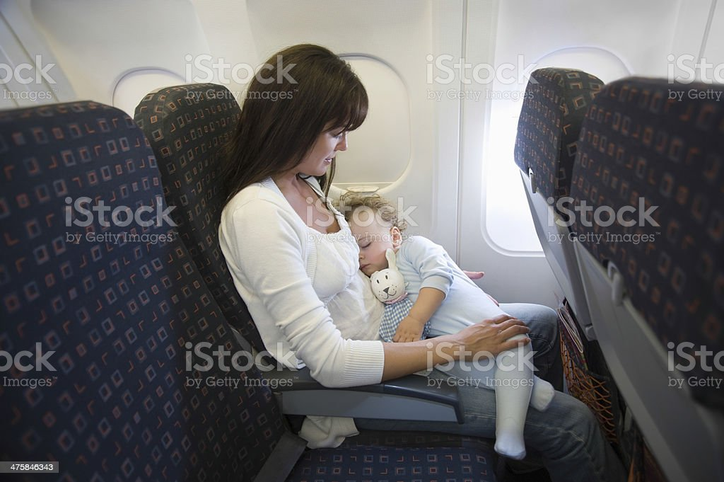 Baby Sleeping On Mother's Laps In Airplane stock photo
