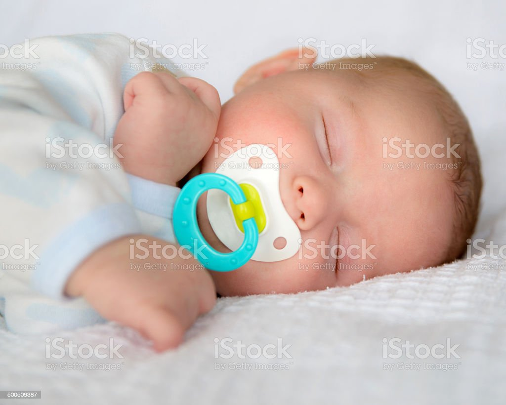 Baby sleeping peacefully with pacifier stock photo