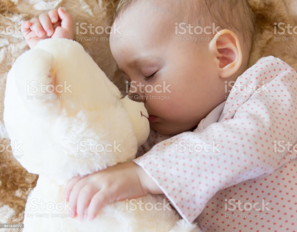 Baby sleeping with teddy bear stock photo