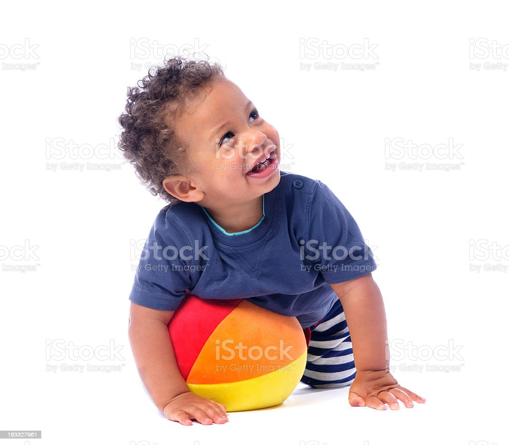 Baby Smiling And Looking Up While Playing With A Ball stock photo