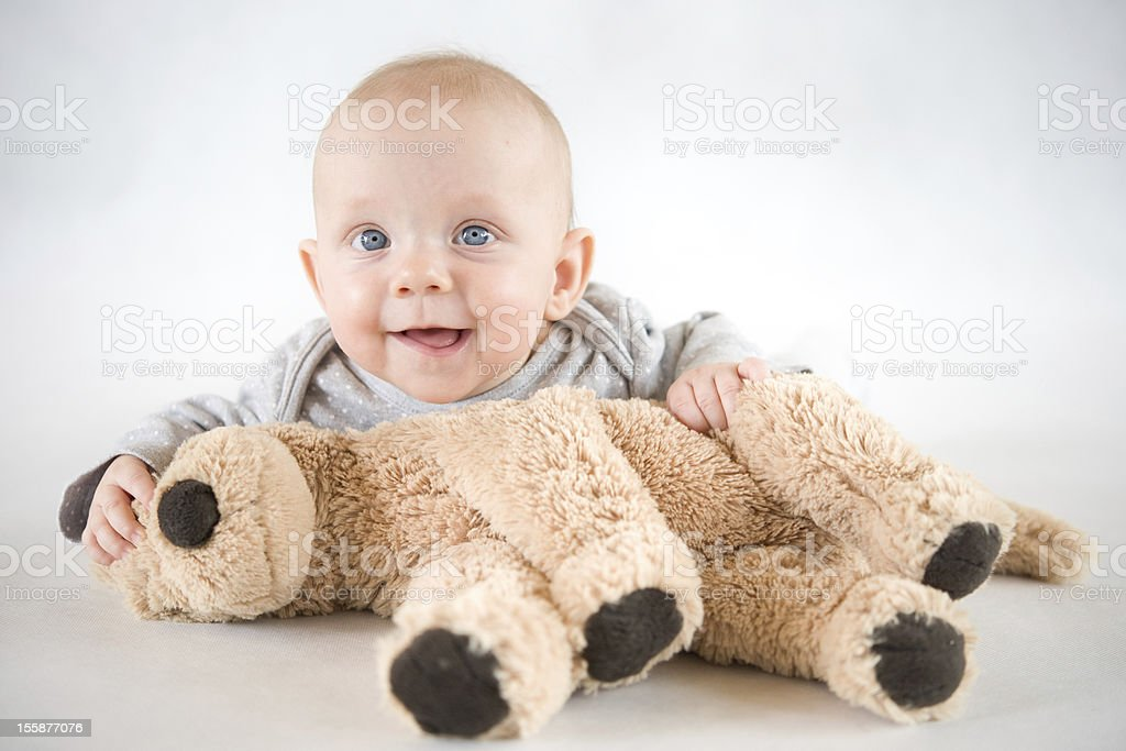 Baby smiling and playing with a soft toy stock photo