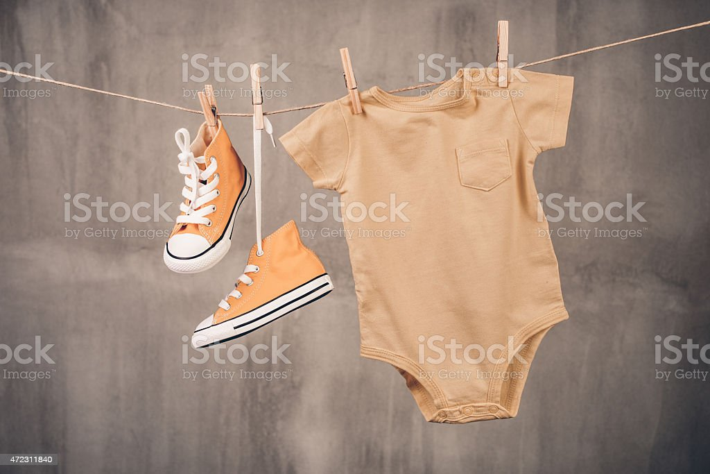 Baby sneakers and onesie stock photo