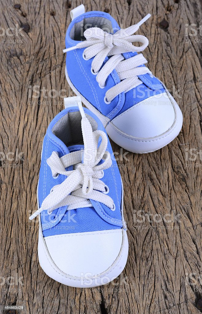 Baby sneakers on wood background stock photo