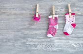 baby socks on rope at wooden background