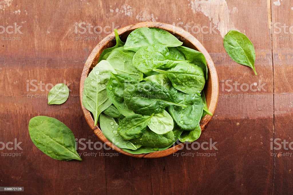 Baby spinach leaves in wooden bowl, organic food, top view stock photo