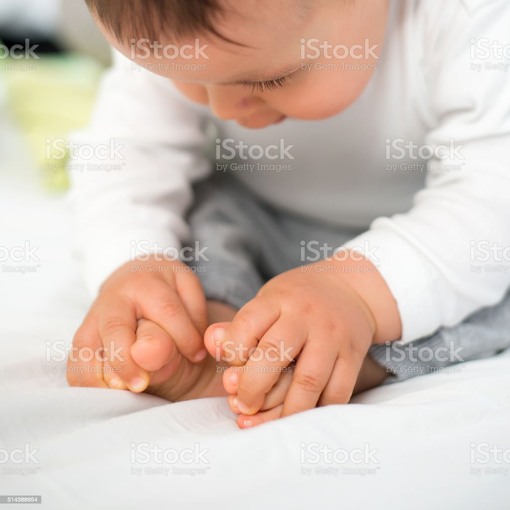 Baby studying his feet. stock photo