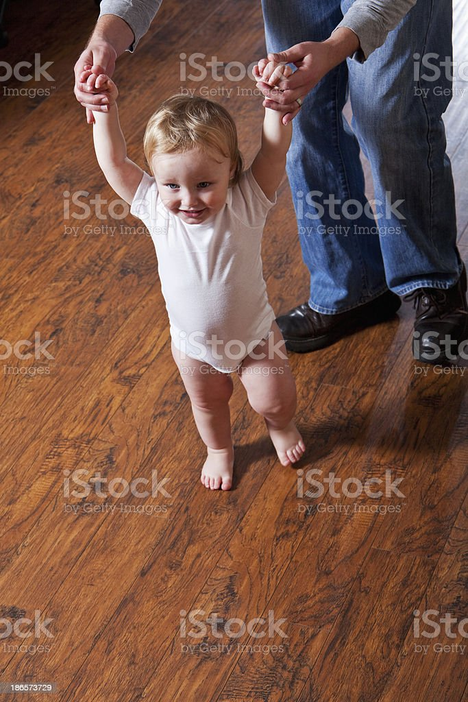 Baby taking first steps stock photo
