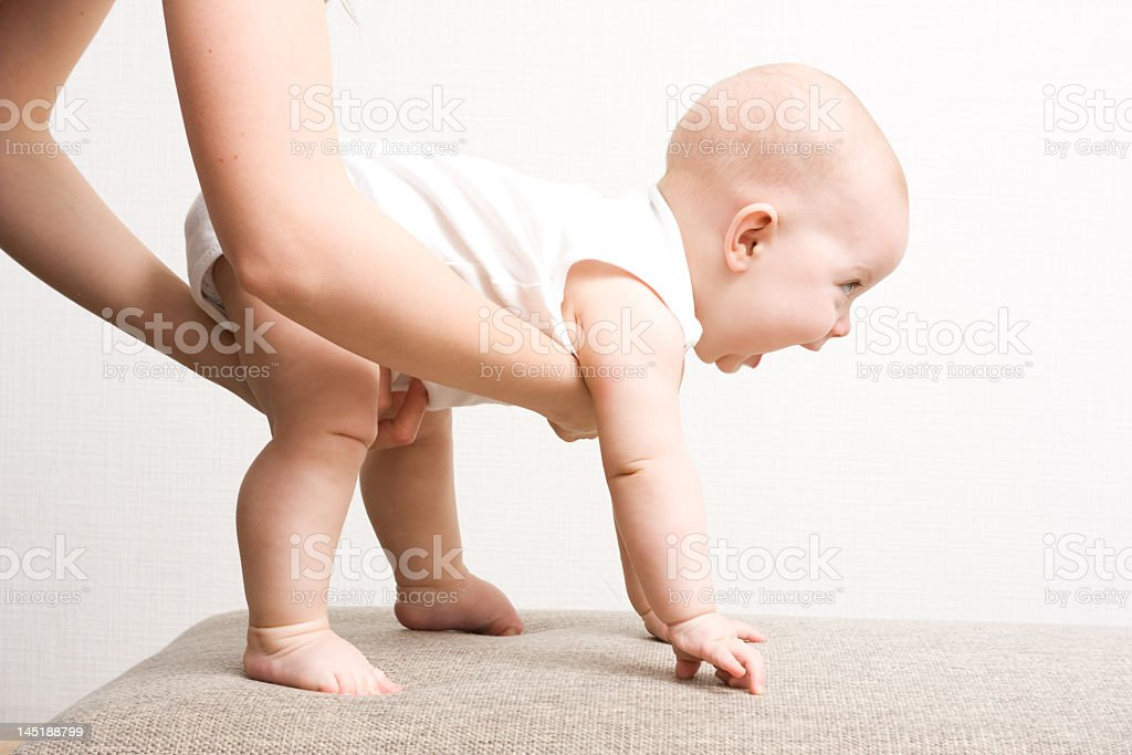 Baby taking first steps whilst supported by mother royalty-free stock photo