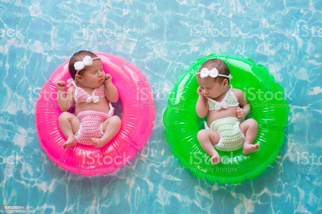 Baby Twin Girls Floating on Swim Rings stock photo