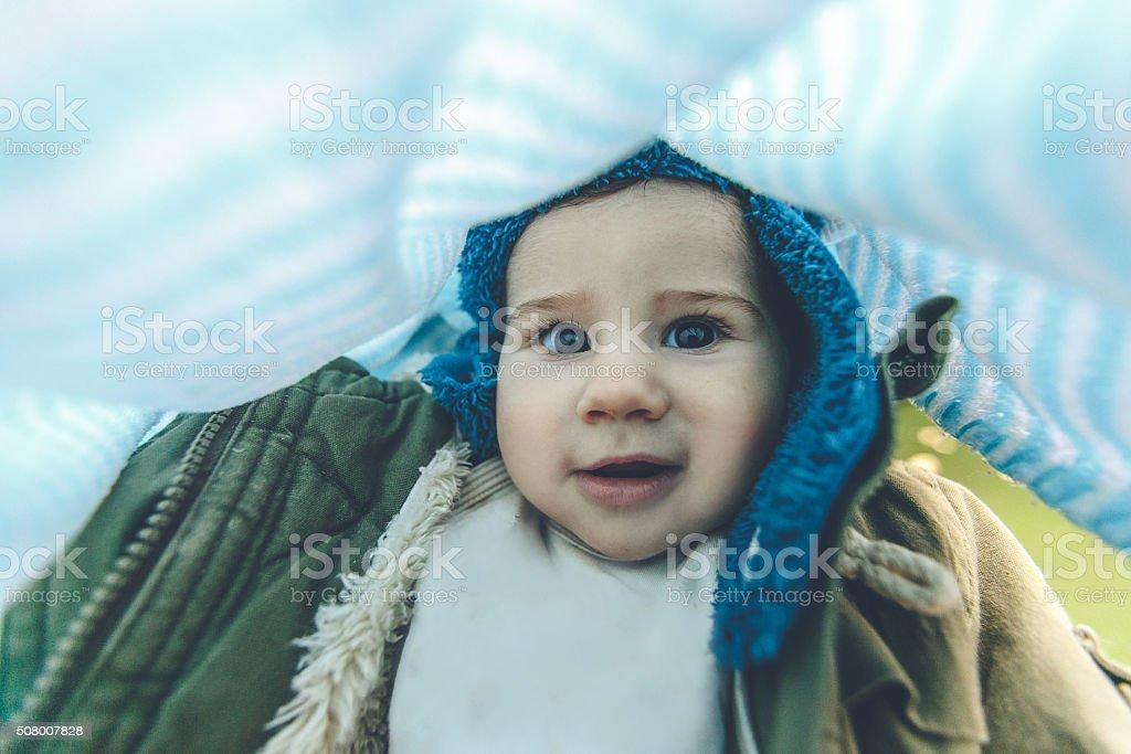 Baby under blanket in stroller stock photo