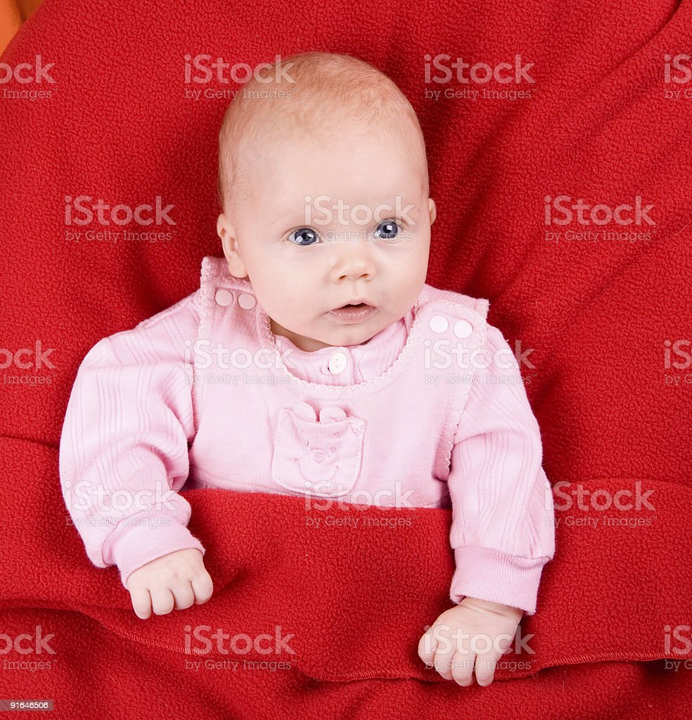 Baby under red blanket stock photo