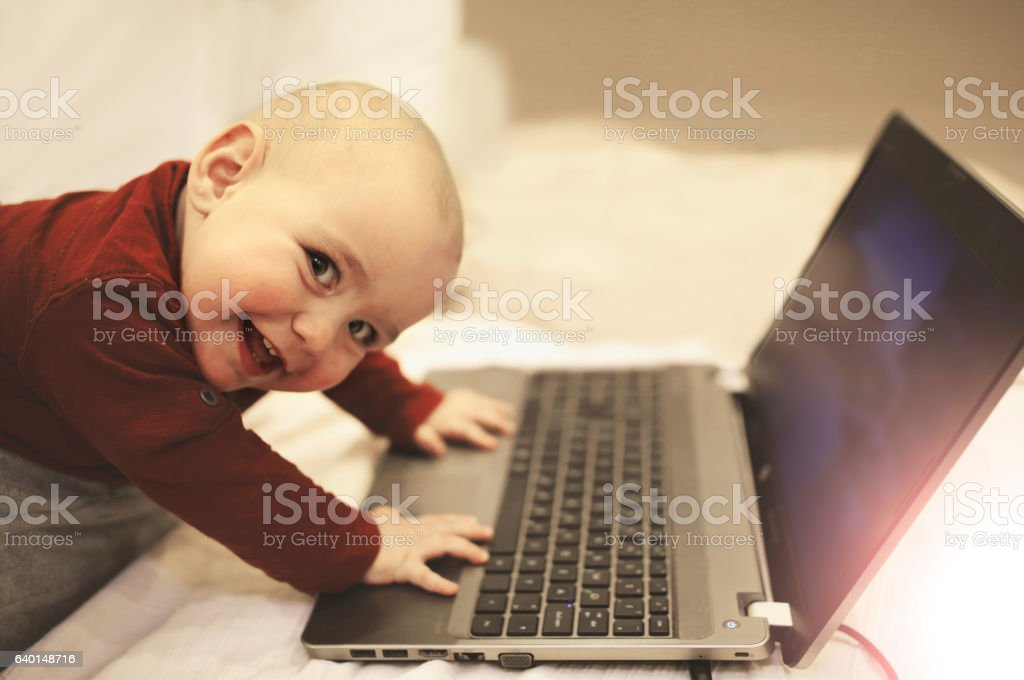Baby using internet on laptop. IT sector is his future. stock photo