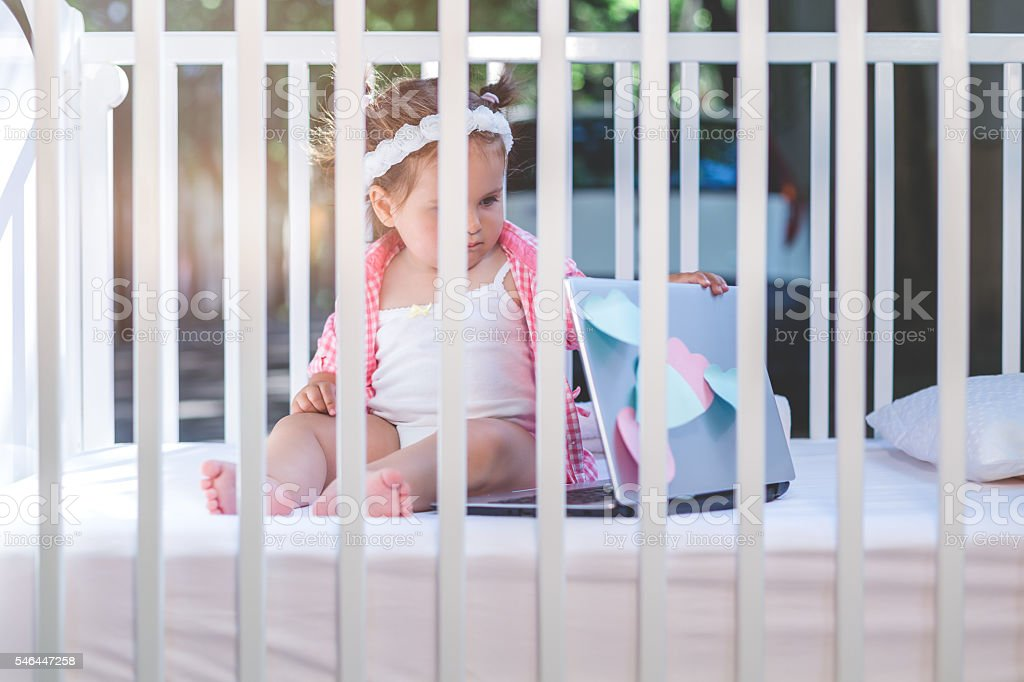 baby using lap top in a crib outside stock photo