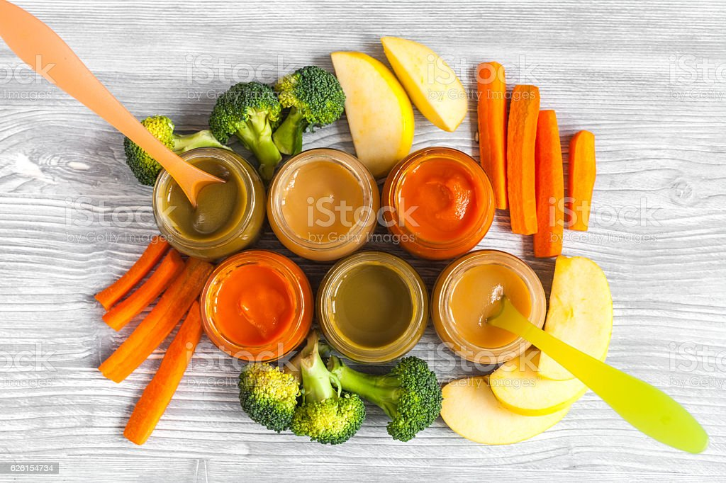 baby vegetable puree on wooden background top view stock photo