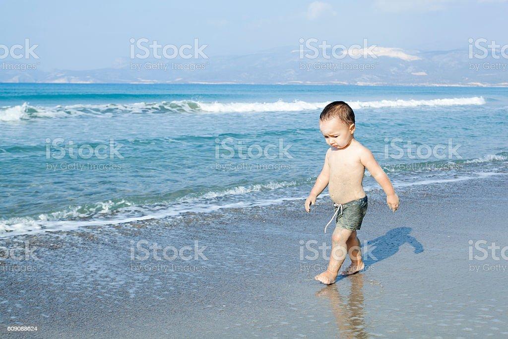Baby Walking on the Beach stock photo