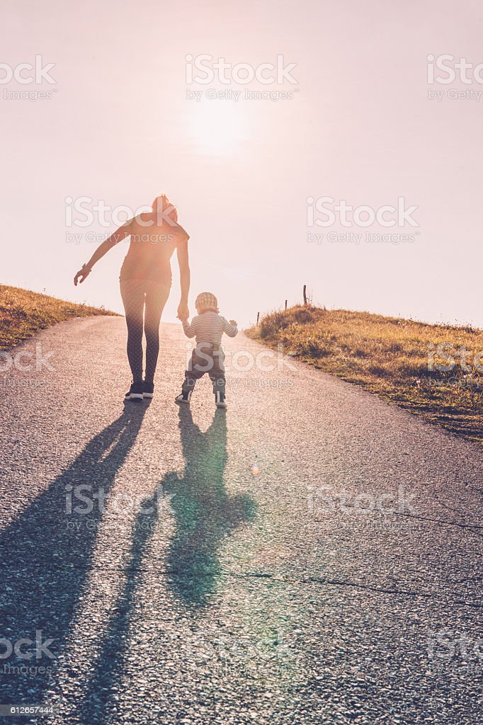 Baby walking with help of its parents - first steps stock photo